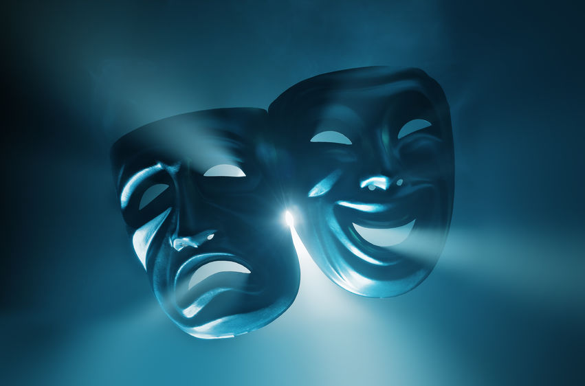 Crying and smiling drama masks in hazy light.
