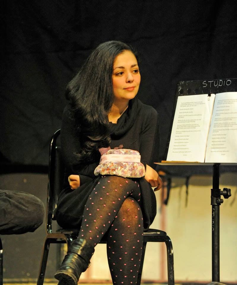 woman seated by a  podium at a staged reading